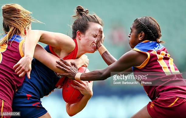 Daisy Pearce of Melbourne is tackled by Emily Bates of Brisbane and Delma Gisu of Brisbane during the 2016 AFL Womens match between the Melbourne...