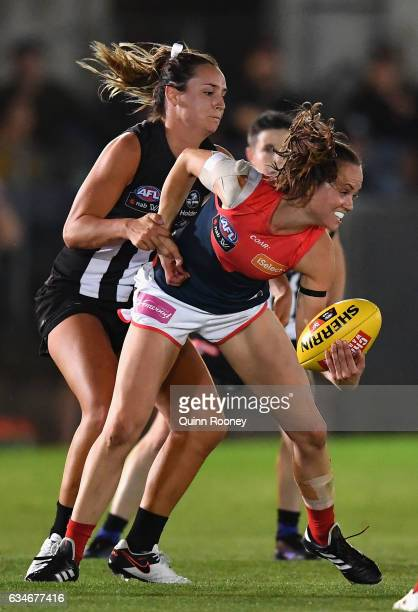 Daisy Pearce of the Demons handballs whilst being tackled during the round two AFL Women's match between the Collingwood Magpies and the Melbourne...