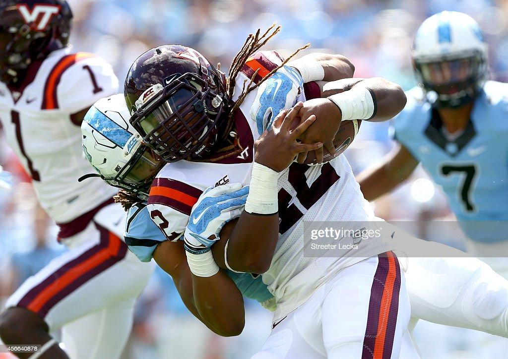Dajaun Drennon #17 of the North Carolina Tar Heels tackles Marshawn Williams #42 of the Virginia Tech Hokies during their game at Kenan Stadium on October 4, 2014 in Chapel Hill, North Carolina.