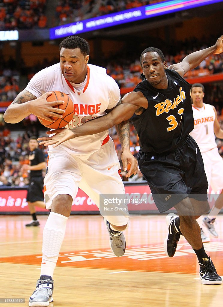 DaJuan Coleman #32 of the Syracuse Orange holds on to the ball as he is chased by Nick Shepard #33of the Long Beach State 49ers during the game at the Carrier Dome on December 6, 2012 in Syracuse, New York.