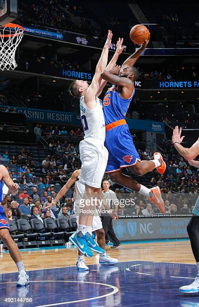 DaJuan Summers of the New York Knicks shoots against Tyler Hansbrough of the Charlotte Hornets on October 17 2015 at Time Warner Cable Arena in...