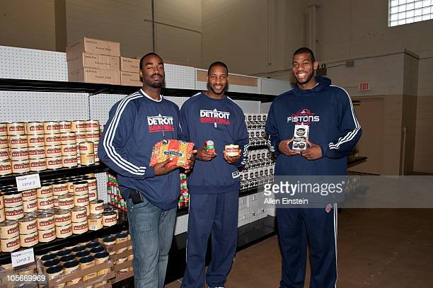 DaJuan Summers Tracy McGrady and Greg Monroe of the Detroit Pistons pose in the grocery aisle during the Detroit Pistons' Feed The Town event at Hope...