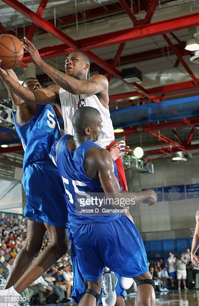 Dajuan Wagner of the Cleveland Cavaliers goes to the basket against Derrick Alston and Derek Hood of the Dallas Mavericks during the Reebok Pro...