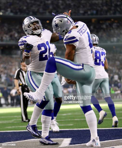 Dak Prescott celebrates his touchdown run with Ezekiel Elliott of the Dallas Cowboys in the fourth quarter against the Green Bay Packers at ATT...