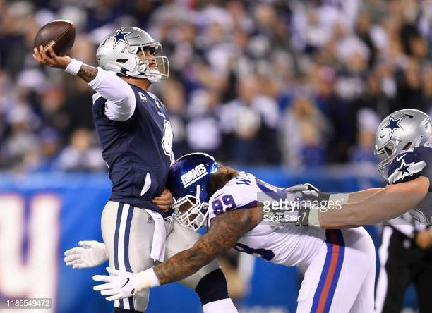 Dak Prescott of the Dallas Cowboys attempts to throw the ball as Leonard Williams of the New York Giants defends during the first quarter of the game...