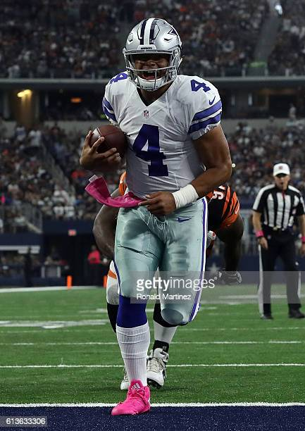 Dak Prescott of the Dallas Cowboys carries the ball into the end zone for a touchdown during the first half against the Cincinnati Bengals at ATT...