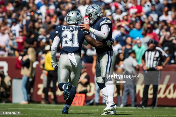 Dak Prescott of the Dallas Cowboys celebrates with Ezekiel Elliott after throwing a pass for a touchdown against the Washington Redskins during the...