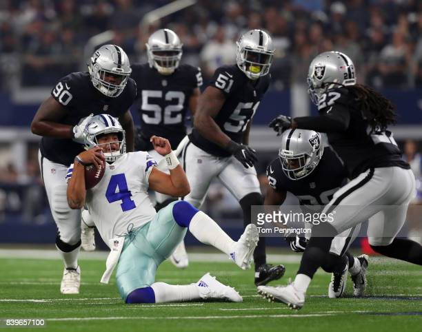 Dak Prescott of the Dallas Cowboys downs the ball under pressure from Oakland Raiders defenders after a carry in the first quarter of a preseason...