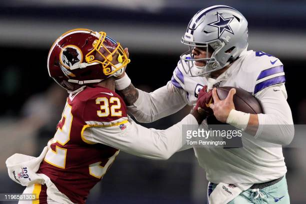Dak Prescott of the Dallas Cowboys fends off a tackle attempt by Jimmy Moreland of the Washington Redskins in the third quarter in the game at AT&T...