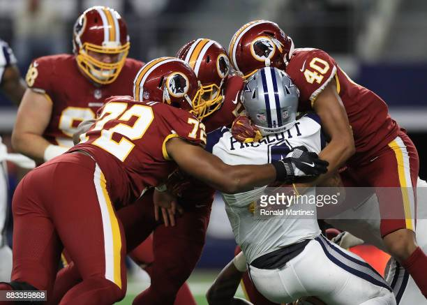 Dak Prescott of the Dallas Cowboys gets sacked by Anthony Lanier II of the Washington Redskins and Josh HarveyClemons of the Washington Redskins in...