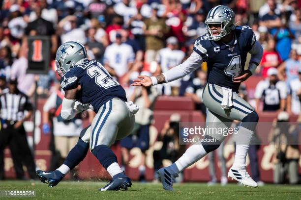 Dak Prescott of the Dallas Cowboys hands the ball off to Ezekiel Elliott against the Washington Redskins during the second half at FedExField on...