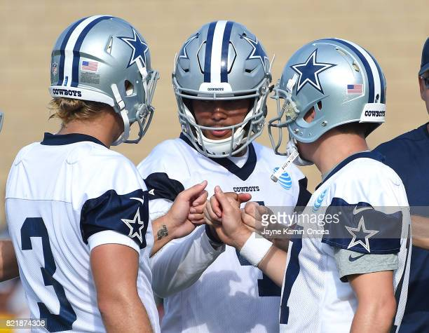 Dak Prescott of the Dallas Cowboys huddles with Zac Dysert and Kellen Moore on the first day of training camp on July 24 2017 in Oxnard California