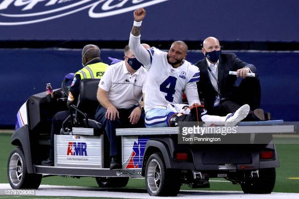 Dak Prescott of the Dallas Cowboys is carted off the field after sustaining a leg injury against the New York Giants during the third quarter at ATT...