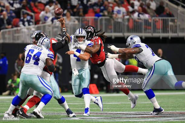 Dak Prescott of the Dallas Cowboys is hit by Adrian Clayborn of the Atlanta Falcons while throwing during the first half at MercedesBenz Stadium on...