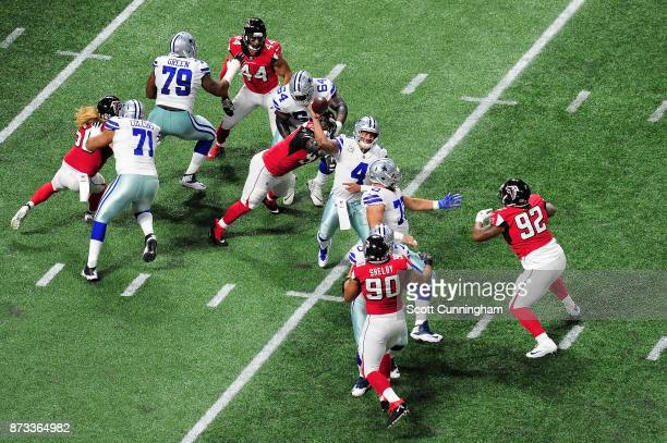 Dak Prescott of the Dallas Cowboys is hit by Adrian Clayborn of the Atlanta Falcons as he throws during the first half at MercedesBenz Stadium on...