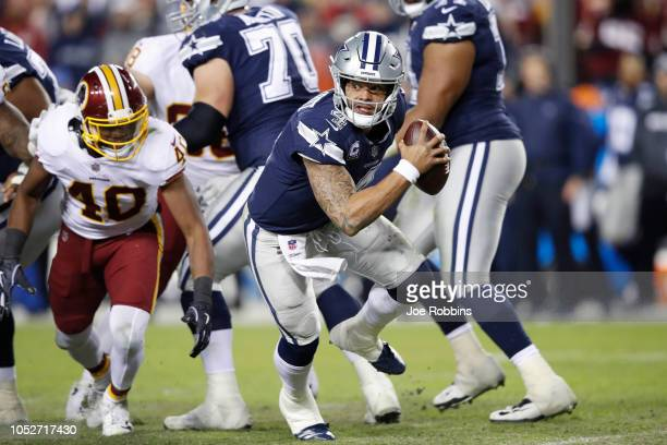 Dak Prescott of the Dallas Cowboys looks to pass while under pressure against the Washington Redskins in the fourth quarter of the game at FedExField...