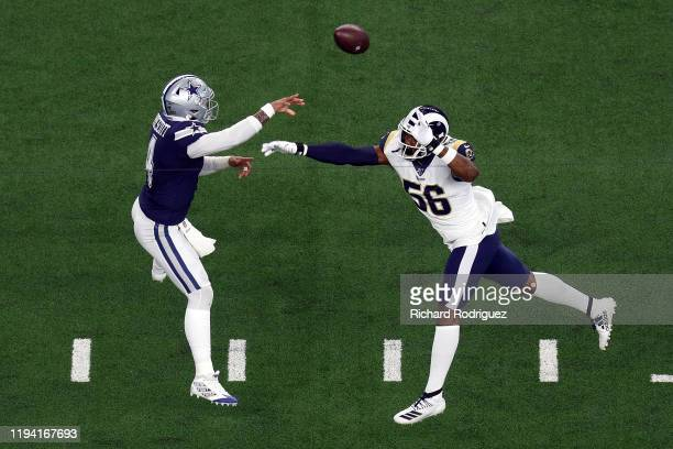 Dak Prescott of the Dallas Cowboys passes under pressure from Dante Fowler of the Los Angeles Rams in the first quarter at AT&T Stadium on December...