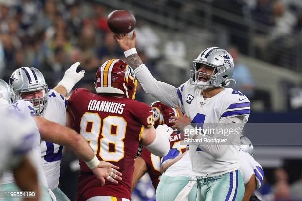 Dak Prescott of the Dallas Cowboys passes under pressure from Matthew Ioannidis of the Washington Redskins at AT&T Stadium on December 29, 2019 in...