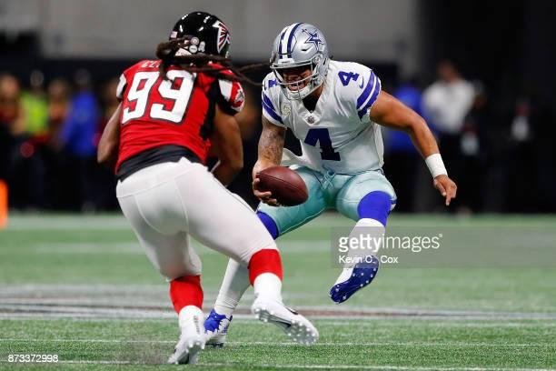 Dak Prescott of the Dallas Cowboys runs away from Adrian Clayborn of the Atlanta Falcons during the first half at MercedesBenz Stadium on November 12...