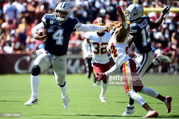 Dak Prescott of the Dallas Cowboys runs in front of Josh Norman of the Washington Redskins during the first half at FedExField on September 15, 2019...