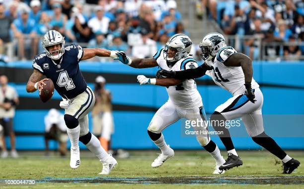 Dak Prescott of the Dallas Cowboys runs the ball againt Shaq GreenThompson and teammate Bryan Cox of the Carolina Panthers in the third quarter...