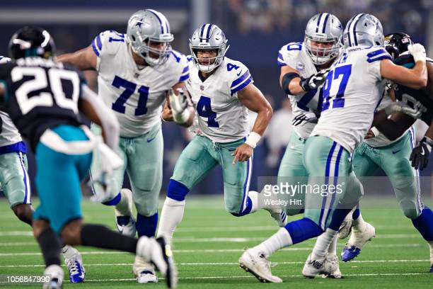 Dak Prescott of the Dallas Cowboys runs the ball behind blockers during a game against the Jacksonville Jaguars at ATT Stadium on October 14 2018 in...