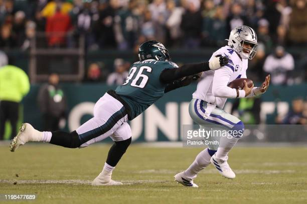 Dak Prescott of the Dallas Cowboys runs with the ball as Derek Barnett of the Philadelphia Eagles is unable to make the tackle during the first half...