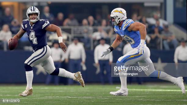 Dak Prescott of the Dallas Cowboys scrambles under pressure from Joey Bosa of the Los Angeles Chargers in the first quarter of a football game at ATT...