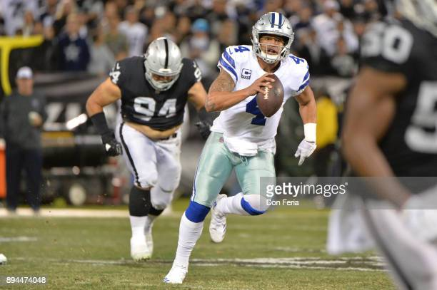 Dak Prescott of the Dallas Cowboys scrambles with the ball against the Oakland Raiders during their NFL game at OaklandAlameda County Coliseum on...