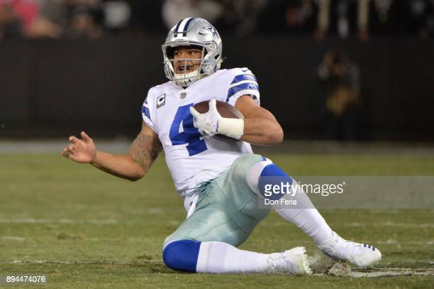 Dak Prescott of the Dallas Cowboys slides during their NFL game against the Oakland Raiders at OaklandAlameda County Coliseum on December 17 2017 in...