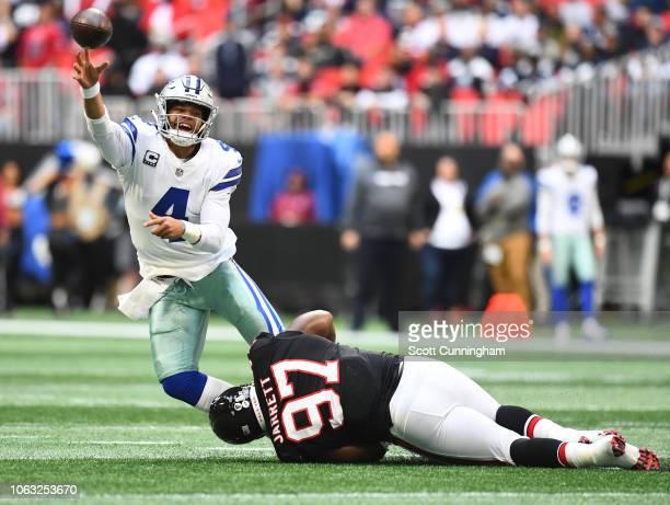 Dak Prescott of the Dallas Cowboys throws a first quarter pass despite pressure by Grady Jarrett of the Atlanta Falcons at Mercedes-Benz Stadium on...