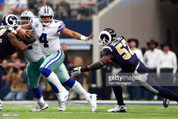 Dak Prescott of the Dallas Cowboys tries to evade Alec Ogletree of the Los Angeles Rams inthe second half of a game at ATT Stadium on October 1 2017...