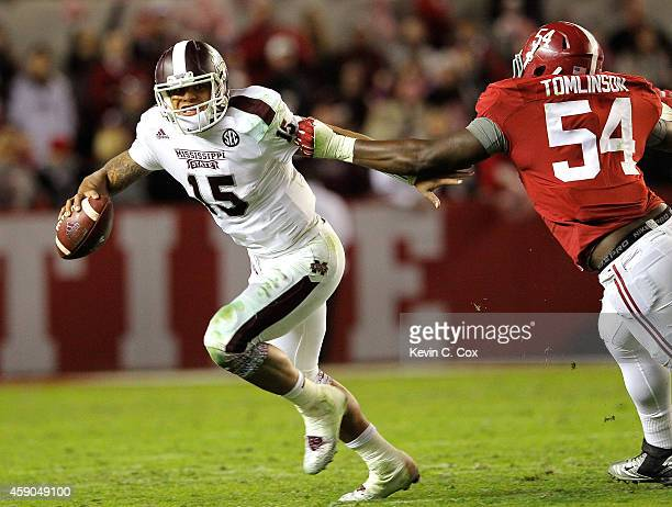 Dak Prescott of the Mississippi State Bulldogs tries to escape a tackle by Dalvin Tomlinson of the Alabama Crimson Tide at BryantDenny Stadium on...