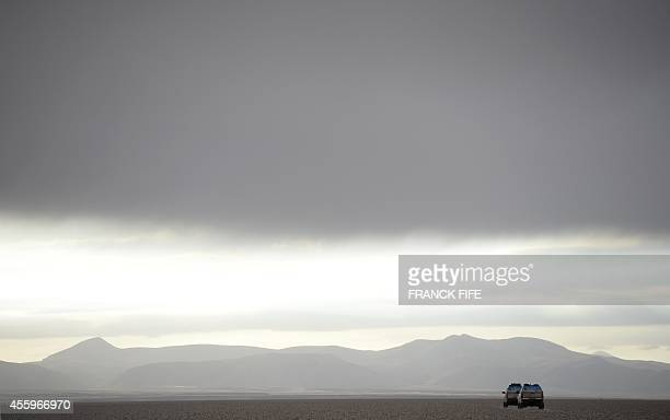 Dakar rally director Etienne Lavigne and Sport director of the Dakar Rally, French David Castera and staff members ride on September 18, 2014 near...
