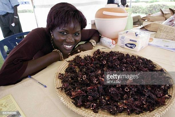 A Senegalese woman poses next to a plate of dried sorrel flowers 19 July 2005 during a local products fair as part of the 4th Forum on Commercial and...