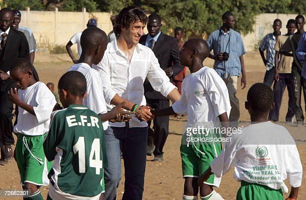 Real Madrid soccer captain and UN goodwill ambassador Raul Gonzalez congratulates children 28 November 2006 after playing a friendly football match...