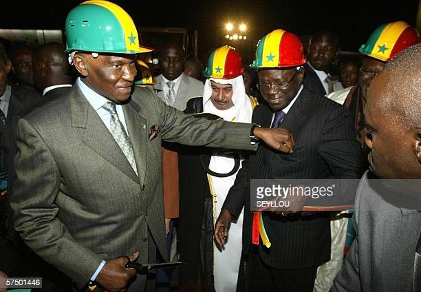 Senegalese President Abdoulaye Wade sticks a piece of inaugural ribbon late 30 April 2006 in the pocket of Dakar Mayor Pape Diop after inaugurating...