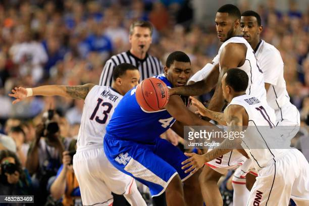 Dakari Johnson of the Kentucky Wildcats battles for a loose ball against Phillip Nolan and Ryan Boatright of the Connecticut Huskies during the NCAA...