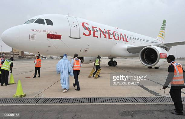 Dakar's airport employee walk next to a Senegal airlines airbus in Dakar on January 19 2011 The new airline company which is equipped with two Airbus...
