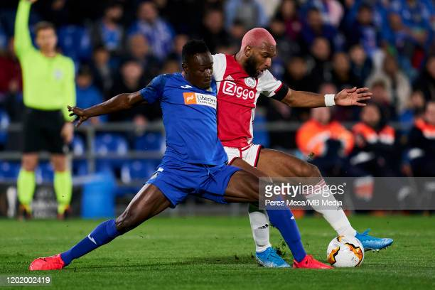 Dakonam Djene of Getafe FC competes for the ball with Ryan Babel of AFC Ajax during the UEFA Europa League round of 32 first leg match between Getafe...