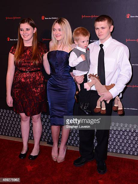 Dakota Fanning poses with LaShawna Long Trenton and Cody Smallwood of Manchester KY at Save the Children's Illumination Gala in New York City on...