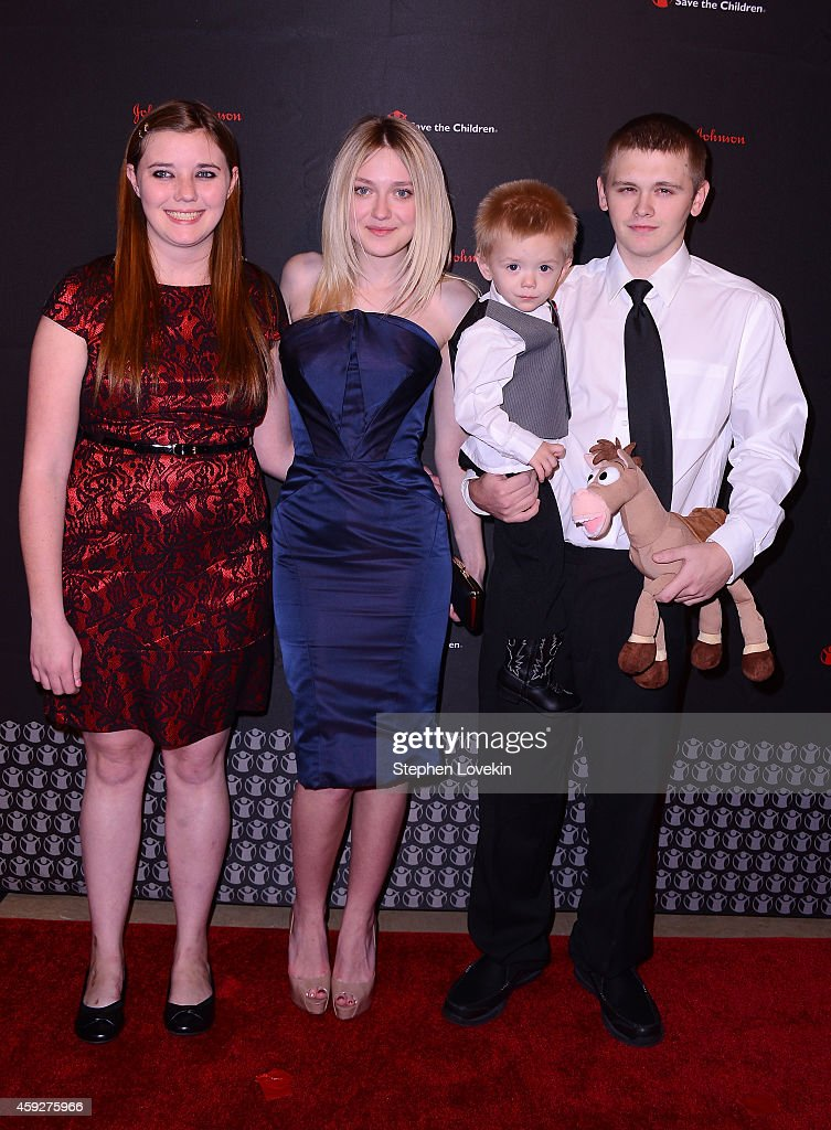 Dakota Fanning poses with (L-R) LaShawna Long, Trenton and Cody Smallwood of Manchester, KY at Save the Children's Illumination Gala in New York City on November 19, 2014. Dakota visited Manchester, KY this past October to learn more about Save the Children's early education programs there. Trenton, 2, is enrolled in Save the Children's home-based Early Steps to School Success program. His parents are coached on activities they can do at home to support their child's growth and development. The program helps children with their language social and emotional development, and prepares children to transition to school.