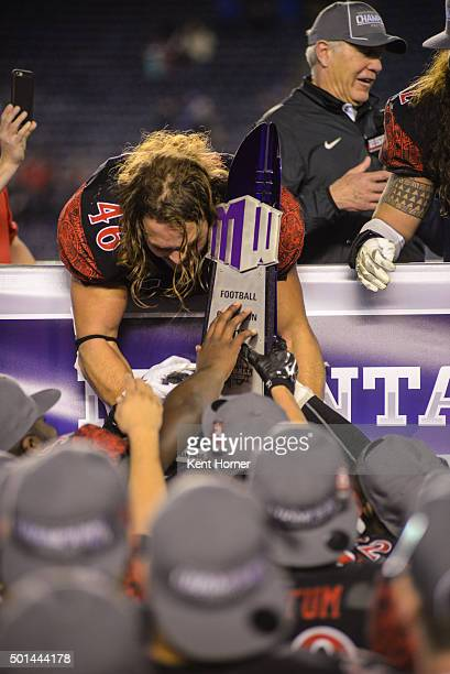 Dakota Gordon of the San Diego State Aztecs holds the champion's trophy after winning the Mountain West Championship game against the Air Force...