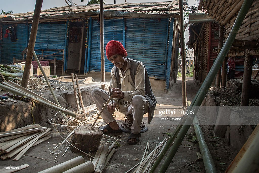 Dal Bahadur Bista, 70 years old, cuts bamboos to make furniture in front of his house in the Beldangi 2 refugee camp on March 14, 2015 in Beldangi, Nepal. Dal arrived 23 years ago after escaping from Bhutan where he was jailed for more than one year after being accused of not paying government taxes. Dal used to work as a tax revenue collector in Bhutan. More than 22,000 Bhutanese refugees still reside in the refugee camps set up in Nepal in the 1990s, after hundreds of thousands of Bhutanese fled the country following a campaign of ethnic cleansing by the Bhutanese Government against the country's ethnic Nepali population. After more than 20 years in Nepal, over 90% of the refugees have been successfully resettled in third countries, thanks to programs by UNHCR and IOM. Those remaining the camps are supported by several organizations that undertake a wide variety of projects. Helped by remittances sent back to Nepal by families already resettled in other countries, the refugees still in the camps have set up their own small businesses in the camps and the roads near them, roads which are also replete with Nepali-owned businesses who benefit directly from the refugees that are still waiting in Nepal to be resettled in third countries.