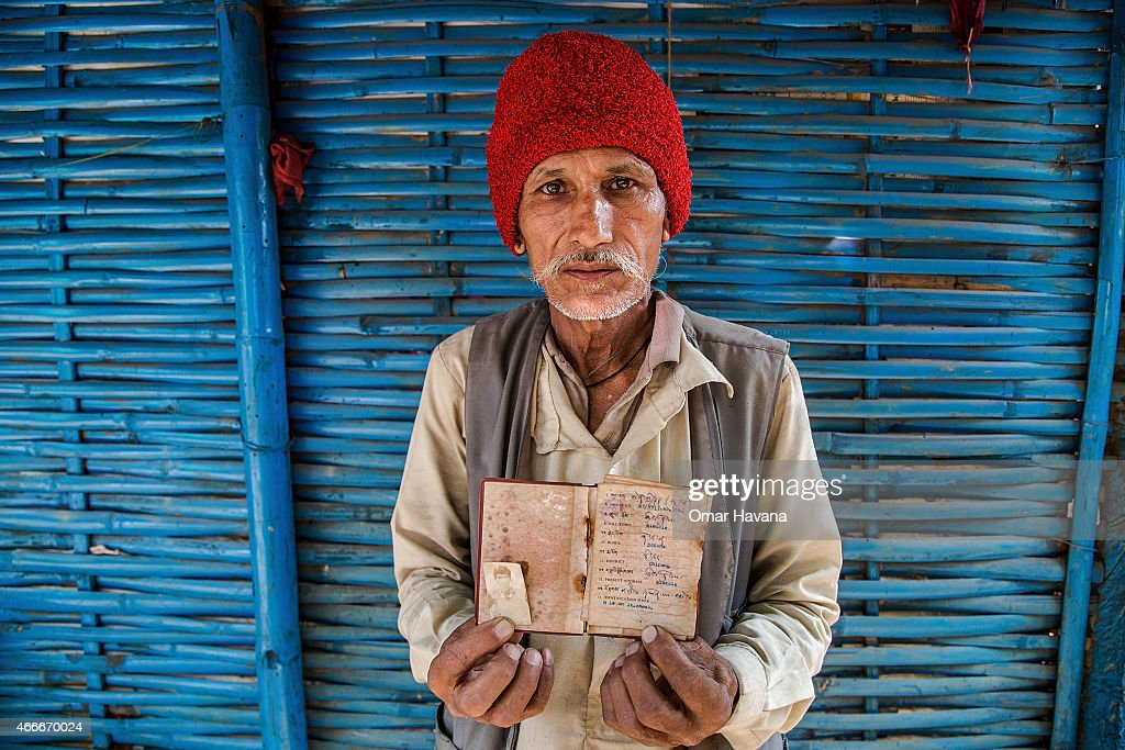 Dal Bahadur Bista, 70 years old, shows his Bhutanese citizenship certificate in front of his house in the Beldangi 2 refugee camp on March 14, 2015 in Beldangi, Nepal. Dal arrived 23 years ago after escaping from Bhutan where he was jailed for more than one year after being accused of not paying government taxes. Dal used to work as a tax revenue collector in Bhutan. More than 22,000 Bhutanese refugees still reside in the refugee camps set up in Nepal in the 1990s, after hundreds of thousands of Bhutanese fled the country following a campaign of ethnic cleansing by the Bhutanese Government against the country's ethnic Nepali population. After more than 20 years in Nepal, over 90% of the refugees have been successfully resettled in third countries, thanks to programs by UNHCR and IOM. Those remaining the camps are supported by several organizations that undertake a wide variety of projects. Helped by remittances sent back to Nepal by families already resettled in other countries, the refugees still in the camps have set up their own small businesses in the camps and the roads near them, roads which are also replete with Nepali-owned businesses who benefit directly from the refugees that are still waiting in Nepal to be resettled in third countries.