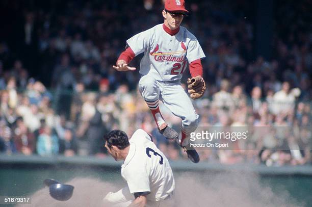 Dal Maxvill of the St Louis Cardinals jumps over Dick McAuliffe of the Detroit Tigers on a play at second base during the World Series at Tiger...