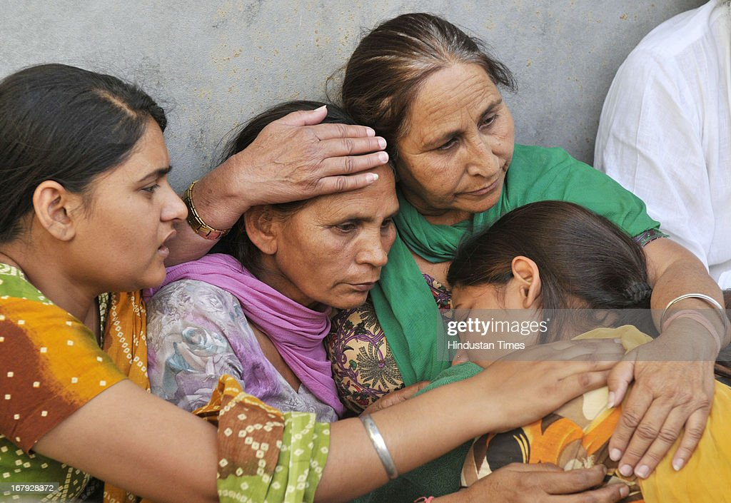 Dalbir Kaur, sister of Sarabjit Singh an Indian prisoner in Pakistan who died in Pakistan hospital after being attacked by fellow inmates console his wife Sukhpreet Kaur, wife and daughters Swapandeep and Poonam at their native house on May 2, 2013 in Bikhiwind about 40 Kms from Amritsar, India. Sarabjit was arrested in 1990 after bombings in Lahore and Faisalabad that killed 14 people and was convicted of spying and carrying out the bomb blasts. His family maintained Singh was innocent and had entered Pakistan inadvertently from his hometown of Bhikiwind in northern Punjab state bordering Pakistan.
