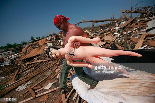 Dale Acker carries a life-size doll that was found while he was helping his mother-in-law dig through her destroyed home on April 30, 2011 in...