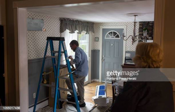 Dale Bois watches from the kitchen as Aaron Sinclair of Dave's World installs a heat pump in her home on September 25 2018 Bois said she and her...