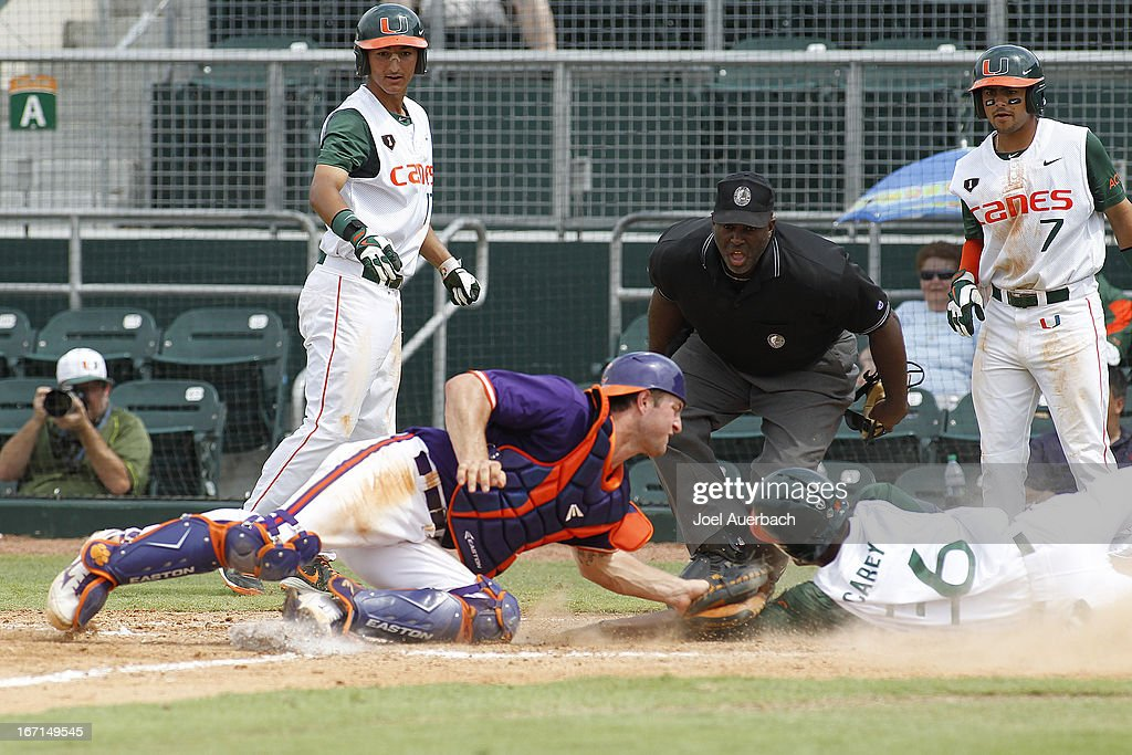 Dale Carey #36 of the Miami Hurricanes is tagged out at home by Garrett Boulware #30 of the Clemson Tigers after he ran from first to third on a triple by Roger Gonzalez #0 (not pictured) in the eighth inning on April 21, 2013 at Alex Rodriguez Park at Mark Light Field in Coral Gables, Florida. Miami defeated Clemson 7-0.